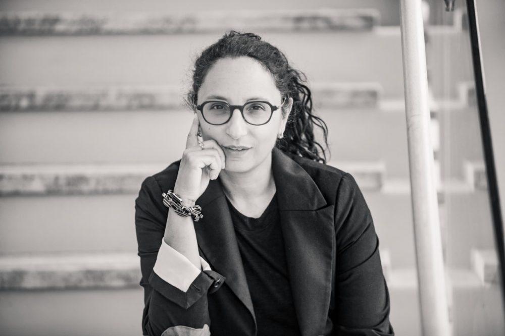 Female professor in glasses sitting on staircase