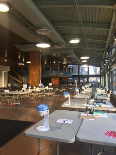 image of interior of university centre with tables set up in rows, each table has a hand santizer on it