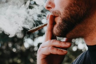 image of person smoking cannabis with puffs of smoke in the air