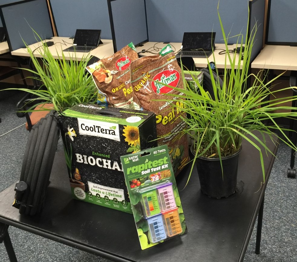 Bags of peat most and other gardening product sit on a table.