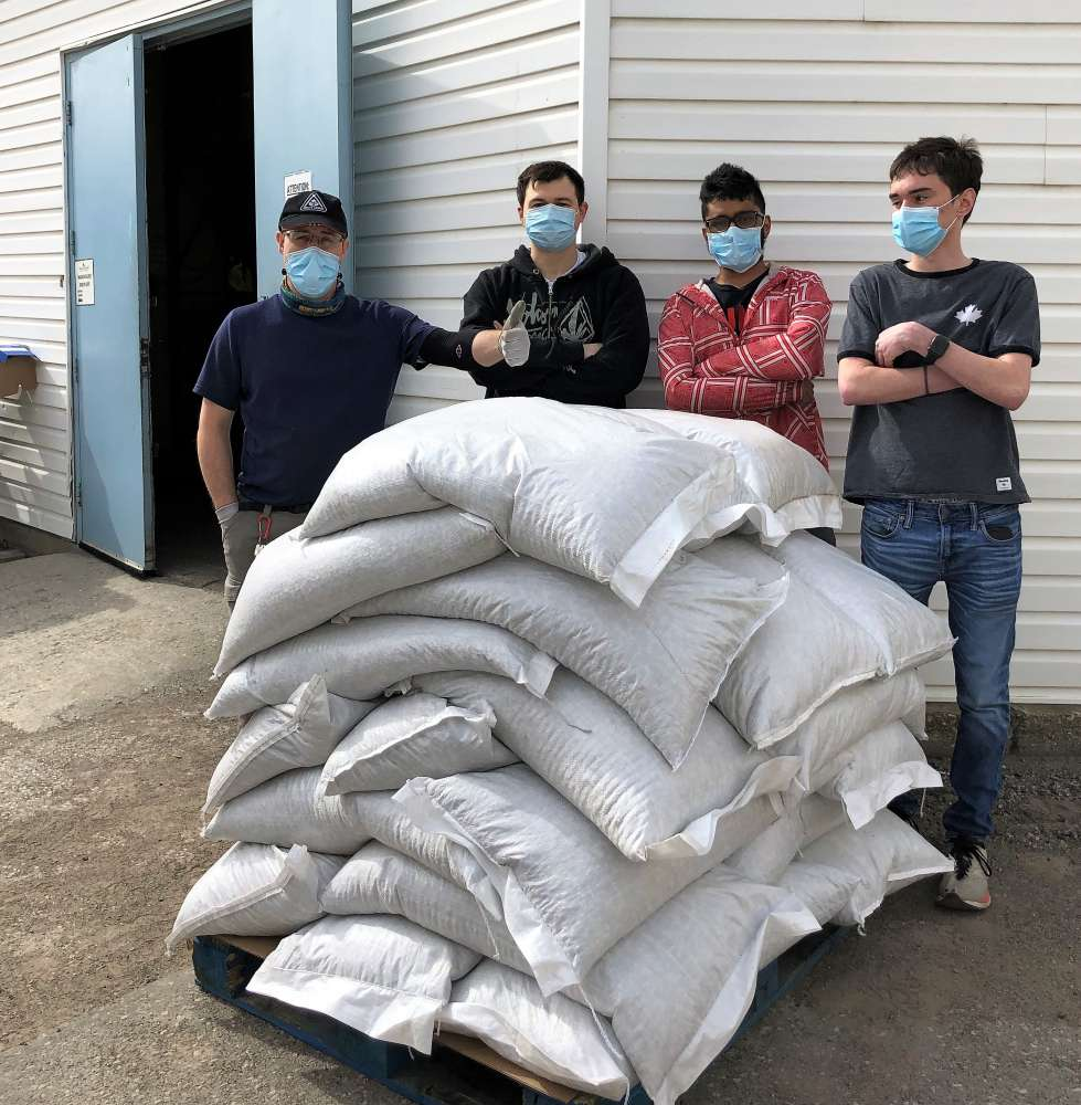 Four men wear masks while standing behind a pallet of large bags of beans