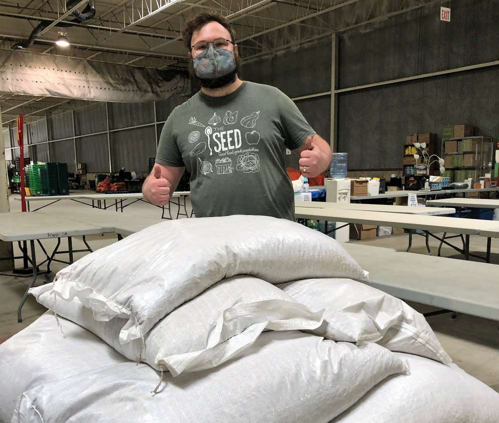 A man gives the thumbs in front of several 70-kg bags of beans in a warehouse.
